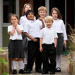 A group of young children in school uniforms standing together.
